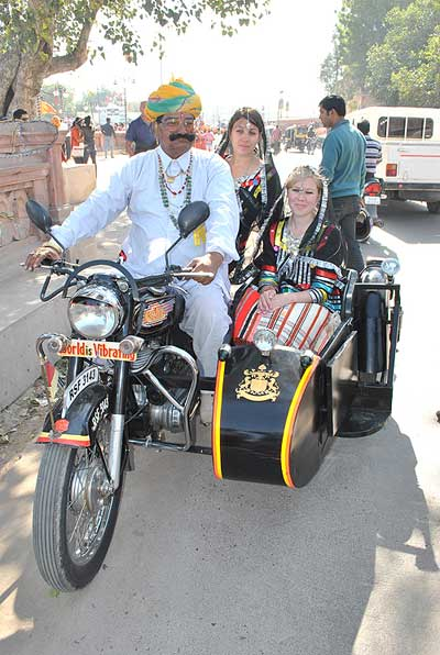 A local man with foreign tourists during Camel Festival 2011 held at Bikaner
