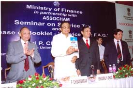 The Union Finance Minister, Shri P Chidambaram releasing a booklet Service Tax: FAQs at a seminar, i