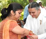 Brahma Kumaris tieing the Rakhi to Arti Dogra