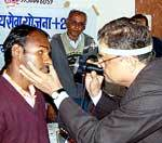 Dr Om Acharya inspecting eyes in Physiotherapist Camp organised in memory of late Buladevi Ranga